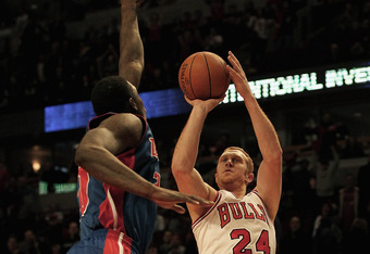 CHICAGO, IL - JANUARY 09: Brian Scalabrine #24 of the Chicago Bulls puts up a shot over Vernon Macklin #20 of the Detroit Pistons at the United Center on January 9, 2012 in Chicago, Illinois. The Bulls defeated the Pistons 92-68. NOTE TO USER: User expres