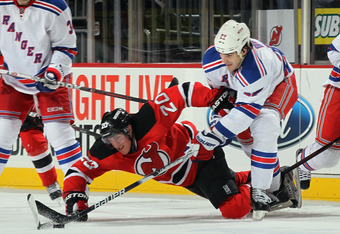 NEWARK, NJ - DECEMBER 20: Brian Boyle #22 of the New York Rangers and Ryan Carter #20 of the New Jersey Devils pursue the puck at the Prudential Center on December 20, 2011 in Newark, New Jersey. The Rangers defeated the Devils 4-1.  (Photo by Bruce Benne