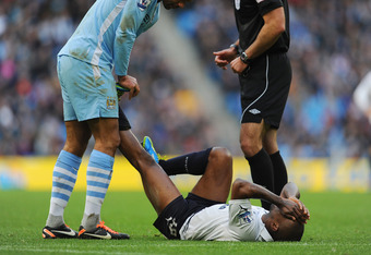MANCHESTER, ENGLAND - JANUARY 22: Joleon Lescott of Manchester City helps Jermain Defoe of Tottenham with a cramp during the Barclays Premier League match between Manchester City and Tottenham Hotspur at the Etihad Stadium on January 22, 2012 in Mancheste