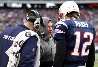 FOXBORO, MA - JANUARY 22:  Tom Brady (R) #12 of the New England Patriots talks with head coach Bill Belichick (C) after a play against the Baltimore Ravens in the first quarter during their AFC Championship Game at Gillette Stadium on January 22, 2012 in