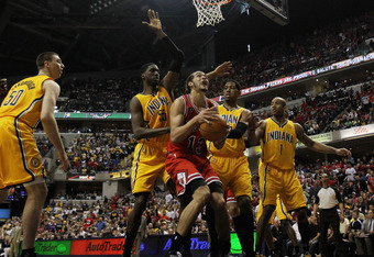 INDIANAPOLIS, IN - APRIL 23: Joakim Noah #13 of the Chicago Bulls goes up for a shot against Roy Hibbert #55, Danny Granger #33 and Dahntay Jones #1 of the Indiana Pacers in Game Four of the Eastern Conference Quarterfinals in the 2011 NBA Playoffs at Con