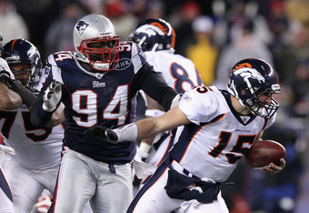 FOXBORO, MA - JANUARY 14:  Shaun Ellis #94 of the New England Patriots sackes Tim Tebow #15 of the Denver Broncos during their AFC Divisional Playoff Game at Gillette Stadium on January 14, 2012 in Foxboro, Massachusetts.  (Photo by Elsa/Getty Images)
