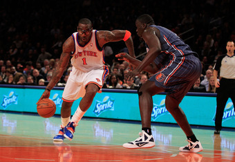 NEW YORK, NY - JANUARY 09:  (L) Amare Stoudemire #1 of the New York Knicks dribbles past (R) DeSagana Diop #7 of the Charlotte Bobcats at Madison Square Garden on January 9, 2012 in New York City. NOTE TO USER: User expressly acknowledges and agrees that,