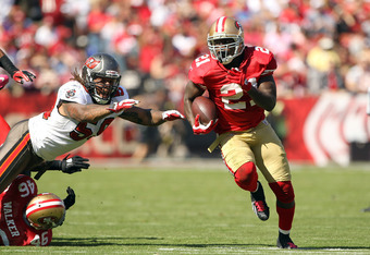 SAN FRANCISCO, CA - OCTOBER 09:   Frank Gore #21 of the San Francisco 49ers runs past a diving  Mason Foster #59 of the Tampa Bay Buccaneers at Candlestick Park on October 9, 2011 in San Francisco, California.  (Photo by Ezra Shaw/Getty Images)