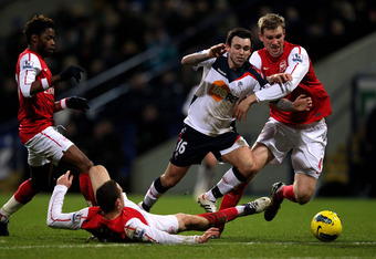 BOLTON, ENGLAND - FEBRUARY 01:  Thomas Vermaelen and Per Mertesacker (R) of Arsenal challenge Mark Davies of Bolton Wanderers during the Barclays Premier League match between Bolton Wanderers and Arsenal at the Reebok Stadium on February 1, 2012 in Bolton