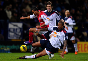BOLTON, ENGLAND - FEBRUARY 01:  Theo Walcott of Arsenal is challenged by Zat Knight of Bolton Wanderers during the Barclays Premier League match between Bolton Wanderers and Arsenal at the Reebok Stadium on February 1, 2012 in Bolton, England.  (Photo by