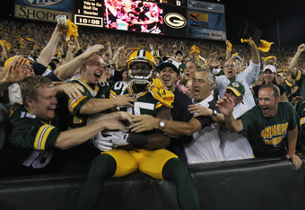 GREEN BAY, WI - SEPTEMBER 08:  Greg Jennings #85 of the Green Bay Packers is mobbed by fans after leaping into the stands following a touchdown catch against the New Orleans Saints during the NFL opening season game at Lambeau Field on September 8, 2011 i