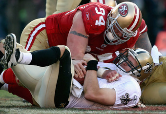 SAN FRANCISCO, CA - JANUARY 14:  Justin Smith #94 of the San Francisco 49ers hovers over Drew Brees #9 of the New Orleans Saints after Brees was sacked in the third quarter of the NFC Divisional playoff game at Candlestick Park on January 14, 2012 in San