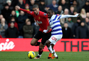 LONDON, ENGLAND - DECEMBER 18:  Chris Smalling of Manchester United and Shaun Wright-Phillips of QPR compete for the ball during the Barclays Premier League match between Queens Park Rangers and Manchester United at Loftus Road on December 18, 2011 in Lon