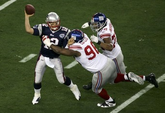 GLENDALE, AZ - FEBRUARY 03:  Quarterback Tom Brady #12 of the New England Patriots is hit as he throws by defensive tackle Barry Cofield #96 and Osi Umenyiora #72 of the New York Giants in the first half during Super Bowl XLII on February 3, 2008 at the U