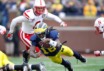 ANN ARBOR, MI - NOVEMBER 19:  Denard Robinson #16 of the Michigan Wolverines dives for extra yards in front of Austin Cassidy #8 of the Nebraska Cornhuskers at Michigan Stadium on November 19, 2011 in Ann Arbor, Michigan. (Photo by Gregory Shamus/Getty Im