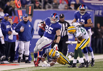 EAST RUTHERFORD, NJ - DECEMBER 04:  Jake Ballard #85 of the New York Giants is knocked out of bounds against Jarrett Bush #24 and Sam Shields #37 of the Green Bay Packers at MetLife Stadium on December 4, 2011 in East Rutherford, New Jersey.  (Photo by Ni
