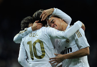MADRID, SPAIN - JANUARY 28:  Mesut Ozil (L) of Real Madrid celebrates with Pepe (R) after scoring Real's 3rd goal during the La Liga match between Real Madrid and Real Zaragoza at Estadio Santiago Bernabeu on January 28, 2012 in Madrid, Spain.  (Photo by