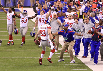 INDIANAPOLIS, IN - FEBRUARY 05:  Chase Blackburn #93 of the New York Giants celebrates with his teammates on the sidelines after an interception over Rob Gronkowski #87 of the New England Patriots from Tom Brady #12  at the 8 yard line in the fourth quart