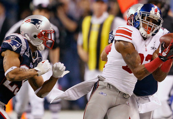 INDIANAPOLIS, IN - FEBRUARY 05:  Mario Manningham #82 of the New York Giants makes a catch on the sidelines against Sterling Moore #29 of the New England Patriots for a gain of 38 yards in the fourth quarter during Super Bowl XLVI at Lucas Oil Stadium on