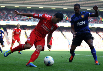 LIVERPOOL, ENGLAND - OCTOBER 15:  Luis Suarez of Liverpool competes with Patrice Evra of Manchester United during the Barclays Premier League match between Liverpool and Manchester United at Anfield on October 15, 2011 in Liverpool, England.  (Photo by Cl