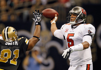NEW ORLEANS, LA - NOVEMBER 06:  Josh Freeman #5 of the Tampa Bay Buccaneers tries to throw around Will Smith #91 of the New Orleans Saints during their game at Mercedes-Benz Superdome on November 6, 2011 in New Orleans, Louisiana.  (Photo by Streeter Leck