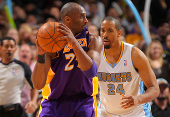 DENVER, CO - FEBRUARY 03:  Kobe Bryant #24 of the Los Angeles Lakers bites his jersey as he controls the ball against Andre Miller #24 of the Denver Nuggets at the Pepsi Center on February 3, 2012 in Denver, Colorado. The Lakers defeated the Nuggets 93-89