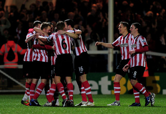 PETERBOROUGH, ENGLAND - JANUARY 08:  Sebastian Larsson (2nd L) of Sunderland is congratulated by teammates after scoring the opening goal during the FA Cup Third Round match between Peterborough United and Sunderland at London Road Stadium on January 8, 2