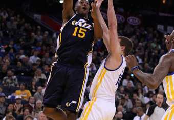 OAKLAND, CA - JANUARY 07:  Derrick Favors #15 of the Utah Jazz shoots over David Lee #10 of the Golden State Warriors at Oracle Arena on January 7, 2012 in Oakland, California.  NOTE TO USER: User expressly acknowledges and agrees that, by downloading and