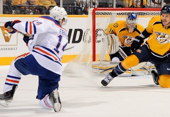 NASHVILLE, TN - NOVEMBER 22:  Jordan Eberle #14 of the Edmonton Oilers first a shot past Shea Weber #6 and onto goalie Pekka Rinne #35 of the Nashville Predators at Bridgestone Arena on November 22, 2011 in Nashville, Tennessee.  (Photo by Frederick Breed