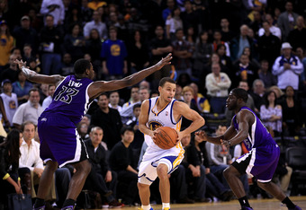 OAKLAND, CA - JANUARY 21:  Stephen Curry #30 of the Golden State Warriors looks to pass while defended by Tyreke Evans #13 and Eugene Jeter #5 of the Sacramento Kings at Oracle Arena on January 21, 2011 in Oakland, California. NOTE TO USER: User expressly