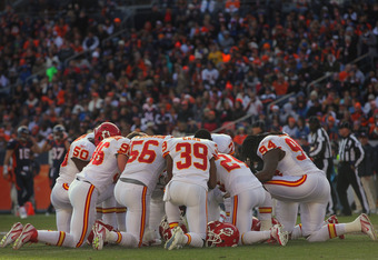 DENVER, CO - JANUARY 01:  The Kansas City Chiefs defense huddle in a moment of silence as Chris Kuper #73 of the Denver Broncos is taken off the field after a leg injury at Sports Authority Field at Mile High on January 1, 2012 in Denver, Colorado. The Ch