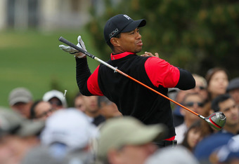 PEBBLE BEACH, CA - FEBRUARY 12:  Tiger Woods lets go of his club as he hits his tee  shot on the tenth hole as a gallery of fans look on during the final round of the AT&T Pebble Beach National Pro-Am at Pebble Beach Golf Links on February 12, 2012 in Peb