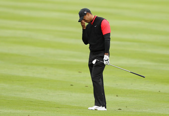 PEBBLE BEACH, CA - FEBRUARY 12:  Tiger Woods reacts after hitting his second shot on the 14th hole during the final round of the AT&T Pebble Beach National Pro-Am at Pebble Beach Golf Links on February 12, 2012 in Pebble Beach, California.  (Photo by Ezra