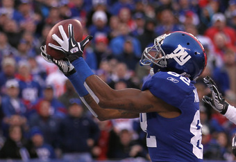 EAST RUTHERFORD, NJ - JANUARY 08:  Mario Manningham #82 of the New York Giants catches a 27-yard touchdown reception in the fourth quarter against Dunta Robinson #23 of the Atlanta Falcons during their NFC Wild Card Playoff game at MetLife Stadium on Janu