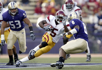 SEATTLE - OCTOBER 22:  Running back Reggie Bush #5 of the USC Trojans rushes against Joe Lobendahn #53 and Dashon Goldson #8 of the Washington Huskies in the first half on October 22, 2005 at Husky Stadium in Seattle, Washington. USC won the game 51-24.