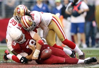 GLENDALE, AZ - DECEMBER 11:  Quarterback John Skelton #19 of the Arizona Cardinals fumbles the football as he is tackled by Aldon Smith #99 and Dashon Goldson #38 of the San Francisco 49ers during the second quarter of the NFL game at the University of Ph