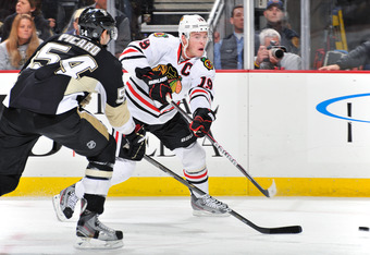 PITTSBURGH, PA - DECEMBER 20:  Jonathan Toews #19 of the Chicago Blackhawks puts a shot on goal in the third period as Alexandre Picard #54 of the Pittsburgh Penguins defends on December 20, 2011 at CONSOL Energy Center in Pittsburgh, Pennsylvania. Pittsb