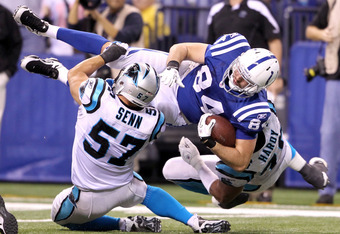 INDIANAPOLIS, IN - NOVEMBER 27:  Jacob Tamme #84 of the Indianapolis Colts is tackled by Jordan Senn#57 and Greg Hardy #76 of the Carolina Panthers at Lucas Oil Stadium on November 27, 2011 in Indianapolis, Indiana.  (Photo by Andy Lyons/Getty Images)