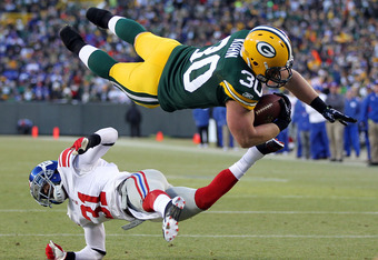 GREEN BAY, WI - JANUARY 15:   John Kuhn #30 of the Green Bay Packers dives in for the touchdown over Aaron Ross #31 of the New York Giants during their NFC Divisional playoff game at Lambeau Field on January 15, 2012 in Green Bay, Wisconsin.  (Photo by Ja