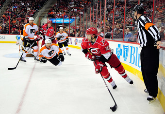 RALEIGH, NC - JANUARY 10:  Tuomo Ruutu #15 of the Carolina Hurricanes moves the puck behind the net as teammate Eric Staal #12 draws a penalty for tripping Kimmo Timonen #44 of the Philadelphia Flyers during play at the RBC Center on January 10, 2012 in R
