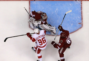 GLENDALE, AZ - APRIL 18:  Goaltender Ilya Bryzgalov #30 of the Phoenix Coyotes makes a save on the shot as Tomas Holmstrom #96 of the Detroit Red Wings skate by in Game Three of the Western Conference Quarterfinals during the 2011 NHL Stanley Cup Playoffs