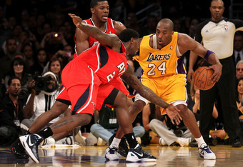 LOS ANGELES, CA - FEBRUARY 14:  Kobe Bryant #24 of the Los Angeles Lakers drives against Marvin Williams #24 and Joe Johnson #2 of the Atlanta Hawks at Staples Center on February 14, 2012 in Los Angeles, California.  The Lakers won 86-78.  NOTE TO USER: U