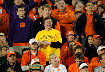 MIAMI GARDENS, FL - JANUARY 04:  A fan of the West Virginia Mountaineers laughs as fans of the Clemson Tigers look on dejected late in the second quarter during the Discover Orange Bowl at Sun Life Stadium on January 4, 2012 in Miami Gardens, Florida.  (P