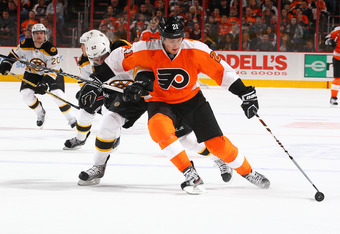 PHILADELPHIA, PA - DECEMBER 17:  James van Riemsdyk #21 of the Philadelphia Flyers skates with the puck as Shawn Thornton #22 of the Boston Bruins defends during their game on December17, 2011 at The Wells Fargo Center in Philadelphia, Pennsylvania.  (Pho