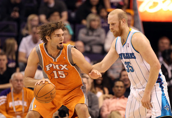 PHOENIX, AZ - DECEMBER 26:  Robin Lopez #15 of the Phoenix Suns handles the ball under pressure from Chris Kaman #35 of the New Orleans Hornets during the season openning NBA game at US Airways Center on December 26, 2011 in Phoenix, Arizona. The Hornets