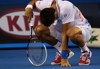 MELBOURNE, AUSTRALIA - JANUARY 29:  Novak Djokovic of Serbia crouches over in his men's final match against Rafael Nadal of Spain during day fourteen of the 2012 Australian Open at Melbourne Park on January 29, 2012 in Melbourne, Australia.  (Photo by Mar
