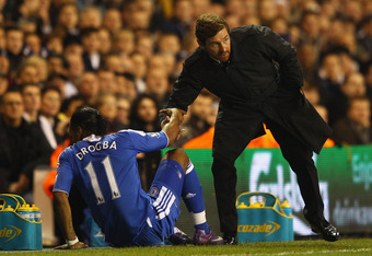 LONDON, ENGLAND - DECEMBER 22:  Manager of Chelsea Andre Villas-Boas helps up Didier Drogba of Chelsea during the Barclays Premier League match between Tottenham Hotspur and Chelsea at White Hart Lane on December 22, 2011 in London, England.  (Photo by Ri