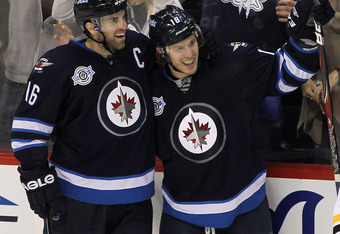WINNIPEG, CANADA - FEBRUARY 17: Andrew Ladd #16 of the Winnipeg Jets congratulates teammate Bryan Little #18 for his third period goal against the Boston Bruins in NHL action at the MTS Centre on February 17, 2012 in Winnipeg, Manitoba, Canada. (Photo by
