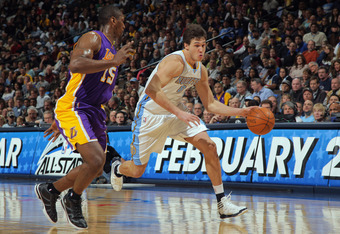 DENVER, CO - FEBRUARY 03:  Danilo Gallinari #8 of the Denver Nuggets dribbles the ball against Metta World Peace #15 of the Los Angeles Lakers at the Pepsi Center on February 3, 2012 in Denver, Colorado. NOTE TO USER: User expressly acknowledges and agree
