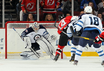 NEWARK, NJ - NOVEMBER 05:  Adam Henrique #14 of the New Jersey Devils scores the overtime goal against Ondrej Pavelec #31 of the Winnipeg Jets at the Prudential Center on November 5, 2011 in Newark, New Jersey. The Devils defeated the Jets 3-2 in overtime