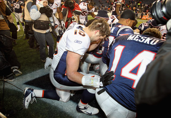 FOXBORO, MA - JANUARY 14:  Tim Tebow #15 of the Denver Broncos kneels and prayers with teammates and members of the New England Patriots after the Patriots won 45-10 during their AFC Divisional Playoff Game at Gillette Stadium on January 14, 2012 in Foxbo
