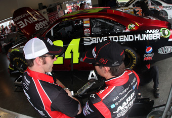 DAYTONA BEACH, FL - FEBRUARY 22:  Jeff Gordon, driver of the #24 Drive to End Hunger Chevrolet, (R) talks with crew chief Alan Gustafson, (L) in the garage during practice for the NASCAR Sprint Cup Series Daytona 500 at Daytona International Speedway on F