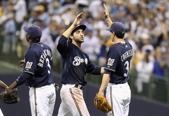 MILWAUKEE, WI - OCTOBER 09: (L-R) Yuniesky Betancourt #3, Ryan Braun #8 and Craig Counsell #30 of the Milwaukee Brewers celebrate after they won 9-6 against the St. Louis Cardinals  during Game one of the National League Championship Series at Miller Park
