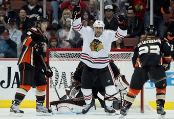 ANAHEIM, CA - FEBRUARY 26:  Jamal Mayers #22 of the Chicago Blackhawks celebrates a goal by teammate Patrick Kane (not pictured) as Luca Sbisa (L) #5 and Francois Beauchemin (R) #23 of the Anaheim Ducks look on in the first period at Honda Center on Febru